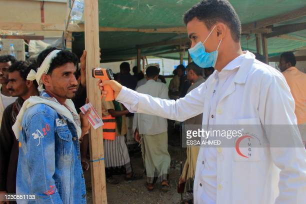 Healthcare worker checks the temperature of displaced Yemenis amid the COVID-19 pandemic, as they arrive to receive humanitarian aid provided by the...