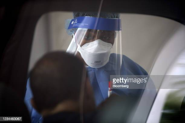 Healthcare worker collects a Covid-19 swab test at a drive-thru testing site outside the Southwest Multi-Service Center in Houston, Texas, U.S., on...