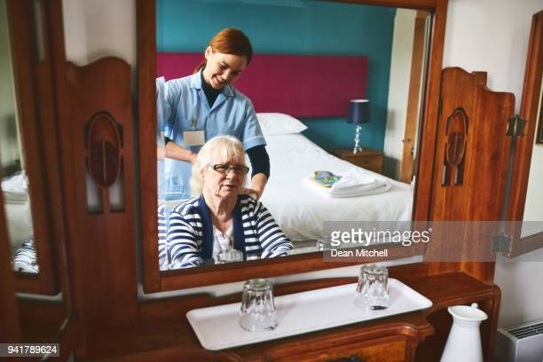 healthcare worker combing hair of a senior female patient - hospice stock pictures, royalty-free photos & images