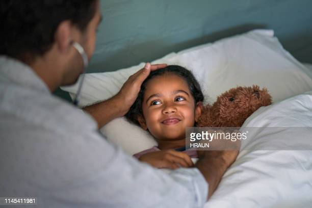 healthcare worker examining patient in bedroom - house call stock pictures, royalty-free photos & images