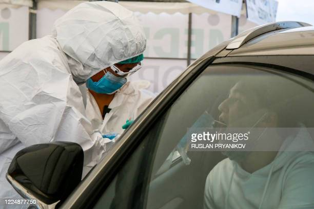 A healthcare worker gives a Covid19 test to a medical staff near Halyk Arena in Almaty on July 5 2020 as Kazakhstan imposed a second round of...