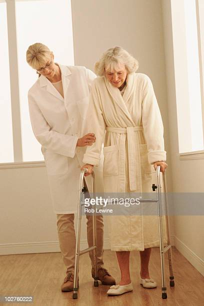healthcare worker helping a woman walk with a walker - hot nurse stock photos and pictures