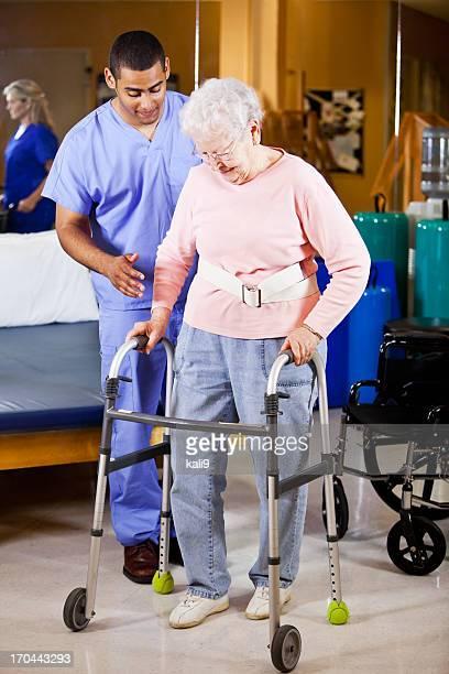 Healthcare worker helping senior woman use walker