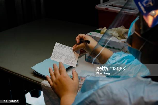 Healthcare worker holds a Covid-19 vaccination card during an event hosted by the Miami Heat at the FTX Arena in Miami, Florida, U.S., on Thursday,...