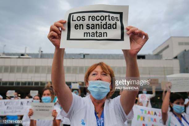 A healthcare worker holds a sign reading Budget cuts in healthcare kill during a gathering outside the Vall d'Hebron Hospital to mark International...