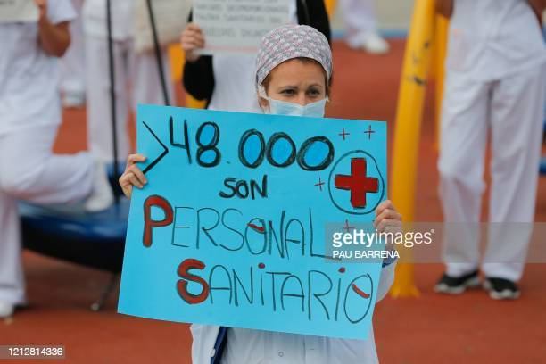 A healthcare worker holds a sign reading More than 48000 are healthcare workers in reference to coronavirus cases during a gathering outside the Vall...