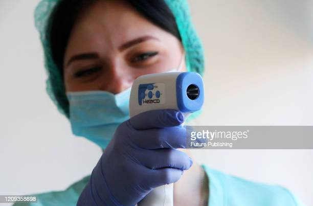 KHARKIV UKRAINE APRIL 7 2020 A healthcare worker holds an infrared thermometer at the Kharkiv Regional Blood Service Centre as servicemen and law...