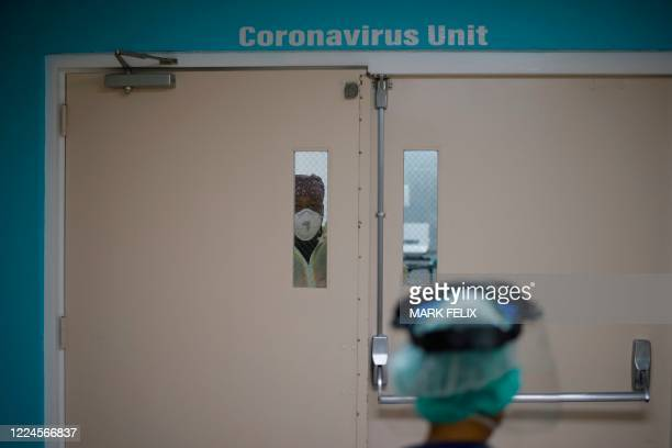 Healthcare worker looks out from a window in the door to the Covid-19 Unit at United Memorial Medical Center in Houston, Texas, July 2, 2020. -...