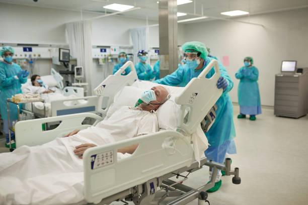 醫護人員將COVID-19病人搬到病床上