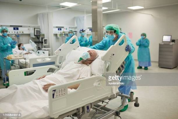 healthcare worker moving covid-19 patient in hospital bed - emergency room stock pictures, royalty-free photos & images