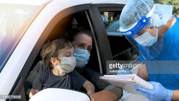 healthcare worker performing a covid-19 test to a mature woman and her son - coronavirus testing stock pictures, royalty-free photos & images