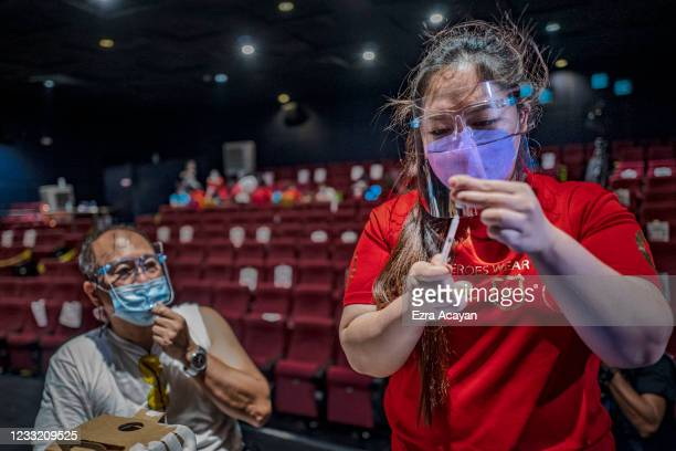 Healthcare worker prepares to administer a dose of Sinovac Biotech's CoronaVac vaccine to an elderly man at a mall theatre converted into a...