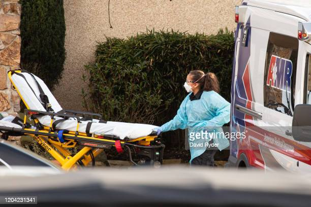 Healthcare worker prepares to transport a patient on a stretcher into an ambulance at Life Care Center of Kirkland on February 29, 2020 in Kirkland,...