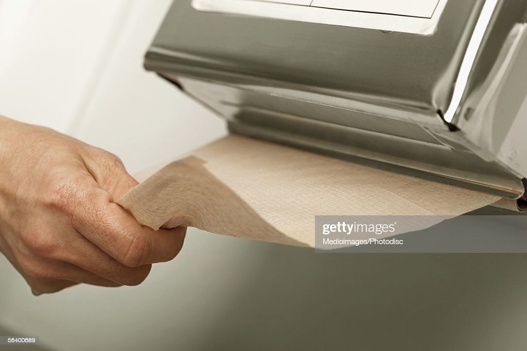 Healthcare worker pulling out paper towel in hospital : Stock Photo