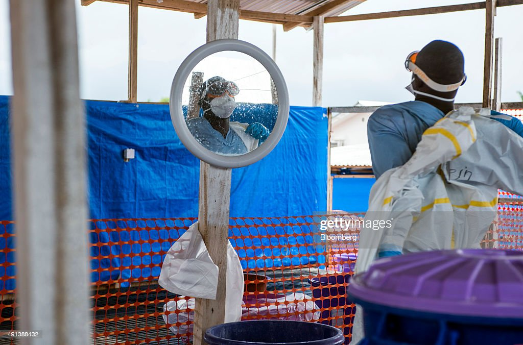 A healthcare worker removes his Personal Protective Equipment (PPE) at an Ebola Treatment Center in Coyah, Guinea, on Thursday, Sept. 10, 2015. An Ebola epidemic and a slump in commodity prices left the International Monetary Fund forecasting no economic growth this year. Photographer: Waldo Swiegers/Bloomberg via Getty Images