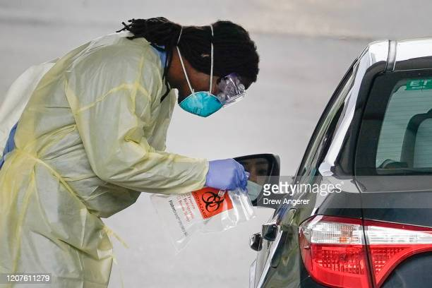 A healthcare worker screens a patient for COVID19 at a drivethrough coronavirus testing site on March 18 2020 in Arlington Virginia Arlington County...