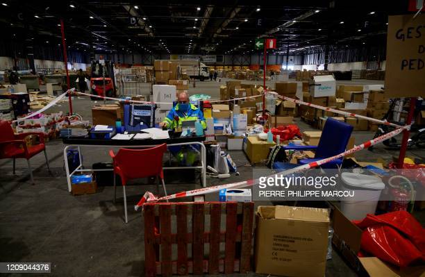A healthcare worker sits at a temporry office surrounded by boxes of medical aid at the Ifema convention and exhibition centre in Madrid on April 03...