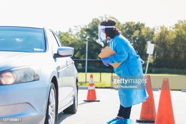 医療従事者がcovid-19検査場でドライバーに話しかける - ドライブスルー検査 ストックフォトと画像