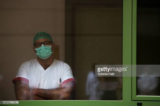 A healthcare worker standing behind a window attends a performance by Italian violinist Fiamma Flavia Paolucci at Tor Vergata Hospital in Rome on May...