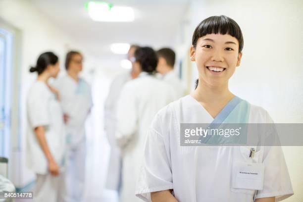 医療従事者の病院の廊下で立っています。