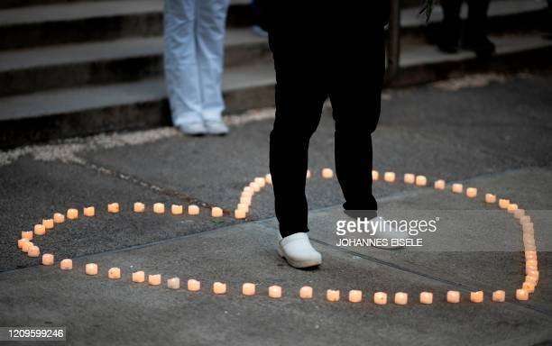 A healthcare worker stands in a heart made with candles as she mourns and remembers her colleagues who died during the outbreak of the novel...