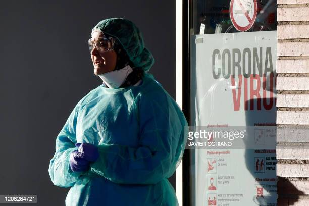 A healthcare worker stands outside the Severo Ochoa hospital in Leganes on March 26 2020 Spain's coronavirus death toll surged above 4000 today but...