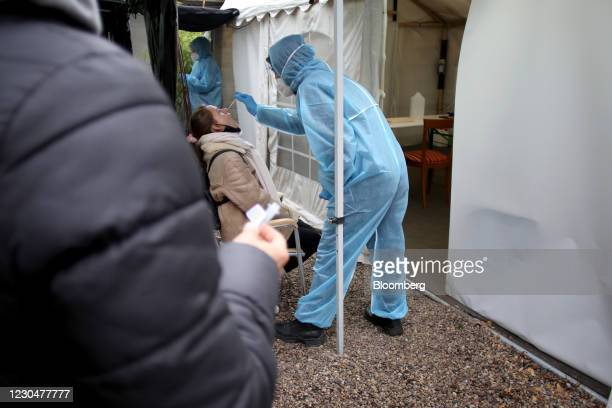 Healthcare worker takes a nasal swab sample during a Covid-19 test at the Kit Kat club which is functioning as a temporary coronavirus testing...