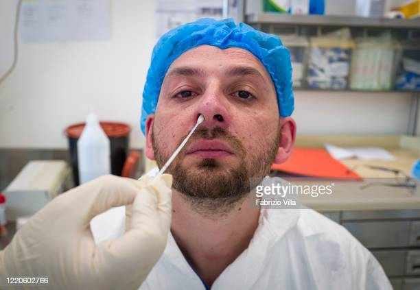 A healthcare worker takes a swab from a nurse in the Infectious Diseases Department of San Marco Hospital in Catania during a periodic coronavirus...