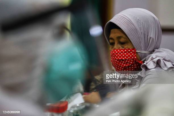 A healthcare worker takes blood samples from a person at Beringharjo market Yogyakarta Indonesia during COVID19 antibody testing June 3 2020