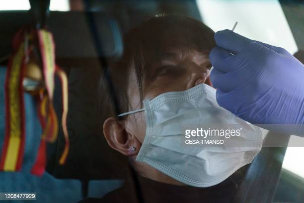 A healthcare worker takes samples from a driver at a drivethrough testing point for the COVID19 disease at the University Hospital in Burgos on March...