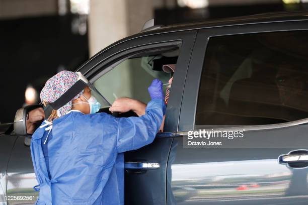 A healthcare worker test a patient at the COVID19 drivethru testing site at the Duke Energy for the Arts Mahaffey Theater on July 8 2020 in St...