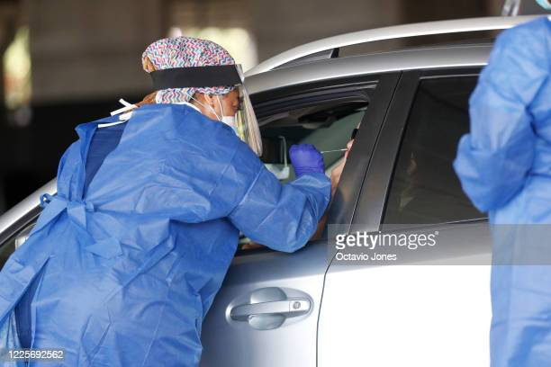Healthcare worker test a patient at the COVID-19 drive-thru testing site at the Duke Energy for the Arts Mahaffey Theater on July 8, 2020 in St....