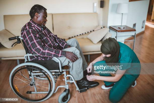 healthcare worker tie shoe laces of disabled senior man. arabian healthcare female worker is helping her disabled afro-american patient - african american man helping elderly stock pictures, royalty-free photos & images