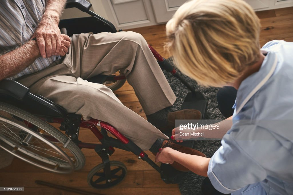 Healthcare worker tie shoe laces of disabled senior man : Stock Photo