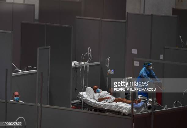 A healthcare worker walks past patients at the temporary hospital for COVID19 patients located at the Ifema convention and exhibition centre in...