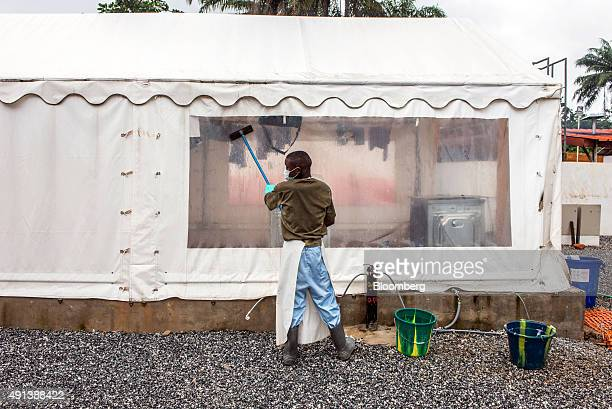A healthcare worker washes a tent screen at an Ebola Treatment Center in Coyah Guinea on Thursday Sept 10 2015 An Ebola epidemic and a slump in...