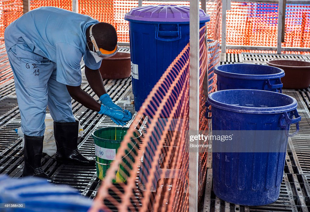 A healthcare worker washes his hands at an Ebola Treatment Center in Coyah, Guinea, on Thursday, Sept. 10, 2015. An Ebola epidemic and a slump in commodity prices left the International Monetary Fund forecasting no economic growth this year. Photographer: Waldo Swiegers/Bloomberg via Getty Images