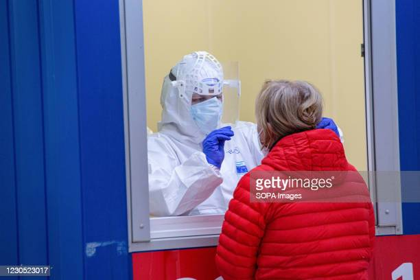 Healthcare worker wearing a personal protective equipment suit , takes a swab sample from a volunteer through a window during the COVID19 mass...