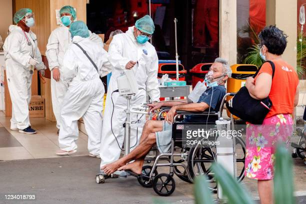 Healthcare worker wearing a personal protective equipment suit attends to a COVID-19 patient with an oxygen mask in a wheel chair outside Bekasi...