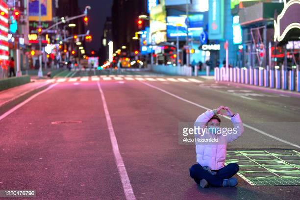 A healthcare worker wearing a protective mask makes a heart with her hands while sitting in the middle of an empty road in Times Square amid the...
