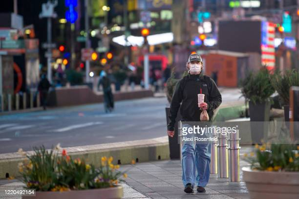 A healthcare worker wearing a protective mask walks through Times Square at night amid the coronavirus pandemic on April 22 2020 in New York City...