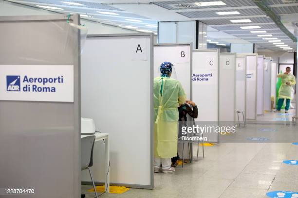 A healthcare worker wearing personal protective equipment collects a swab sample from a passenger at the Covid19 rapid test facility at Fiumicino...