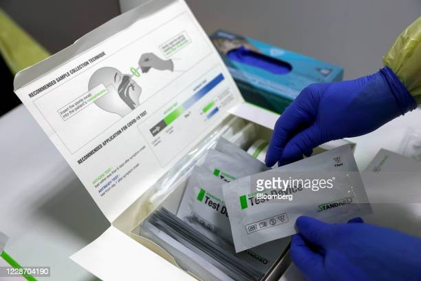 A healthcare worker wearing personal protective equipment holds test devices to collect swab samples at the Covid19 rapid test facility at Fiumicino...