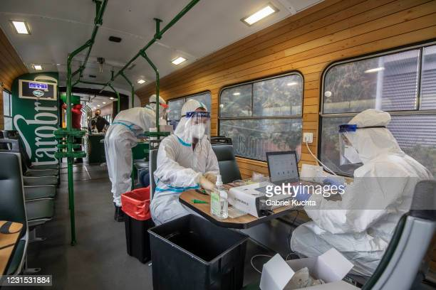 Healthcare worker wearing personal protective equipment tests an employee of the public transport company during mandatory testing for COVID-19 on a...