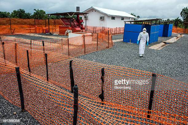 A healthcare worker wearing Personal Protective Equipment walks from cleaning tent Ebola Treatment Center in Coyah Guinea on Thursday Sept 10 2015 An...