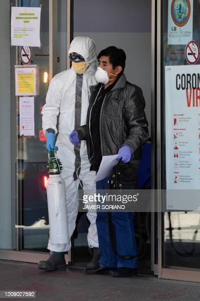 A healthcare worker wearing protective suit helps a patient at the Severo Ochoa Hospital in Leganes near Madrid on April 03 before his transfert to...