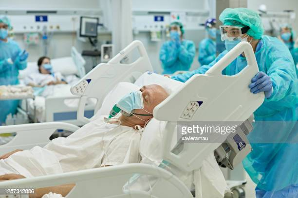 healthcare worker wheeling covid-19 patient in hospital bed - state of emergency stock pictures, royalty-free photos & images