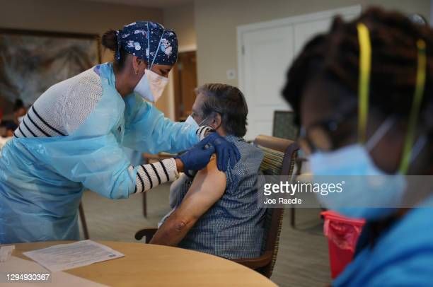 Healthcare worker with American Medical Response, Inc working with the Florida Department of Health in Broward administers a Pfizer-BioNtech COVID-19...