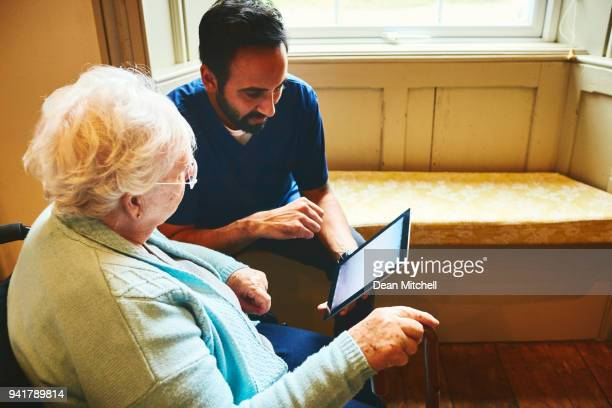 Healthcare worker  with senior woman using digital tablet