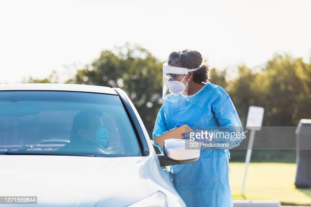 医療従事者は、covid-19試験場で男性に関する情報を書きます - ドライブスルー検査 ストックフォトと画像